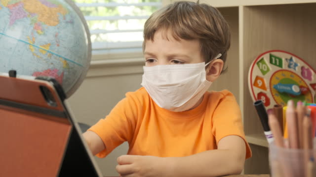 little boy wearing a protective face mask using a digital tablet - preschool student stock videos & royalty-free footage