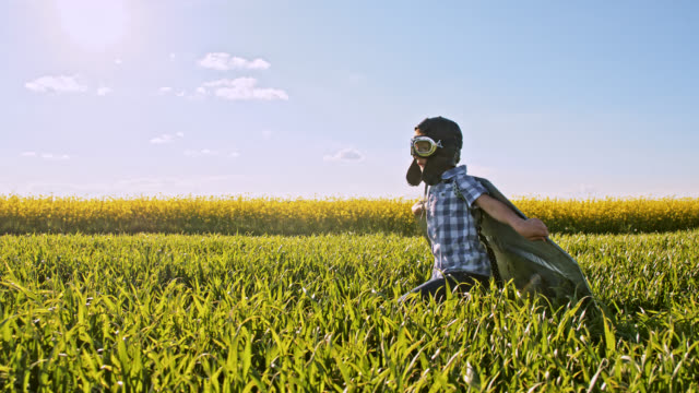 SLO MO Little boy wearing an airplane costume while running in a wheat field