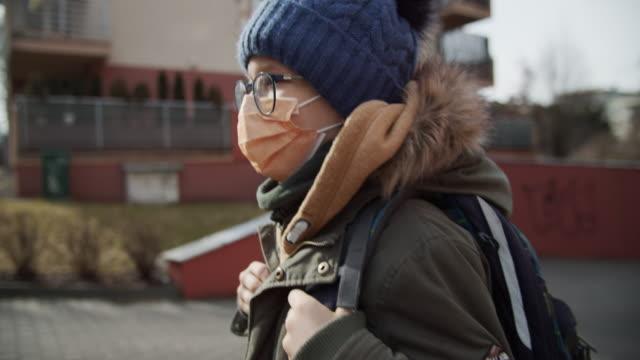 stockvideo's en b-roll-footage met weinig jongen die antivirusmasker draagt dat naar school gaat - bril brillen en lenzen