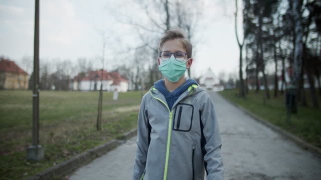 vídeos de stock e filmes b-roll de little boy wearing anti virus mask is walking in the park - 10 11 anos