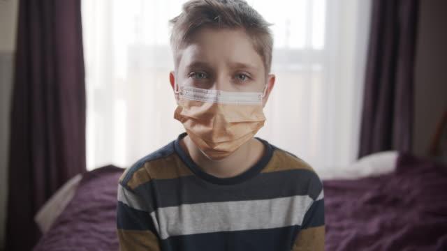 vídeos de stock e filmes b-roll de little boy wearing anti virus mask staying at home - máscara cirúrgica