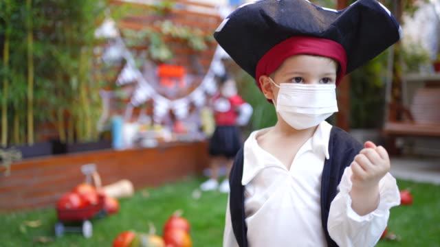 stockvideo's en b-roll-footage met weinig jongen die gezichtsmasker op partij van halloween tijdens de pandemie covid-19 draagt - graaf dracula