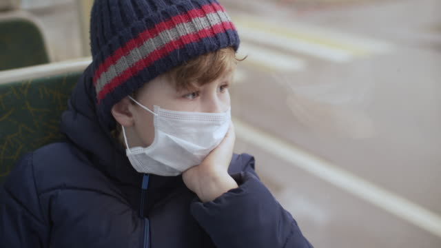 little boy wearing protective medical mask travels in bus - bus stock videos & royalty-free footage