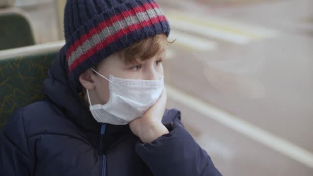 kleiner junge mit schutzärztlicher schutzmaske fährt im bus - bus stock-videos und b-roll-filmmaterial
