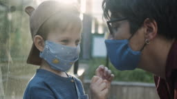 Little boy wearing reusable protective fabric mask helps his father to put on his mask