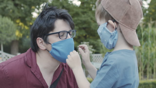 little boy wearing reusable protective fabric mask helps his father to put on his mask - getting dressed stock videos & royalty-free footage