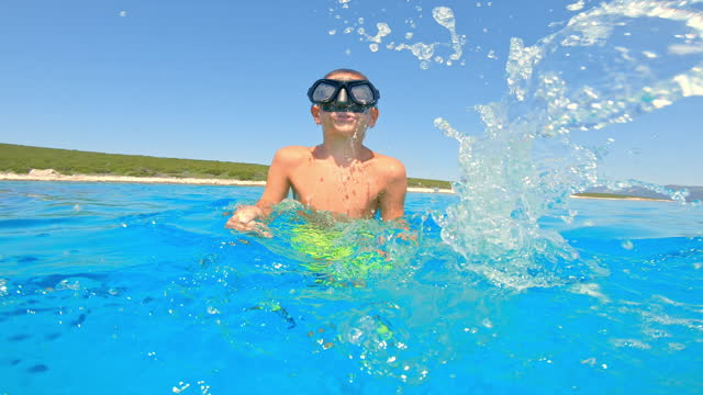 日差しの中で海に飛び込む前にダイビングマスクの波を持つ小さな男の子 - クロアチア点の映像素材/bロール