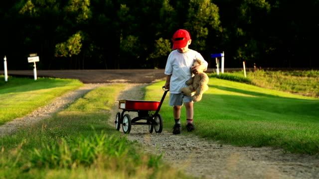 vídeos y material grabado en eventos de stock de little boy with a red wagon, carretera de campo - gorra de béisbol