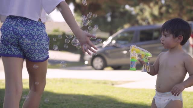 Jongetje met Bubble Gun spelen met zijn zusters