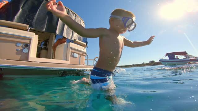 在陽光明媚的日子里, 戴著潛水面具的小男孩從船上跳入水中 - 少於10秒 個影片檔及 b 捲影像