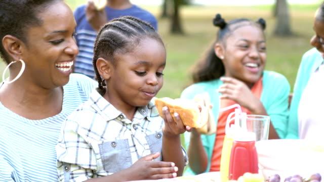 バーベキューでホットドッグを食べて、家族の小さな男の子 - ホットドッグ点の映像素材/bロール