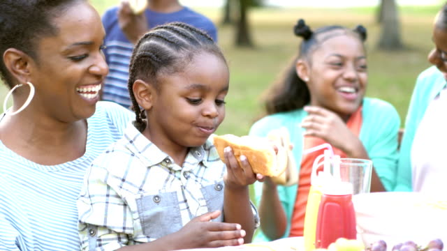vídeos de stock e filmes b-roll de little boy with family, eating hotdog at cookout - hot dog