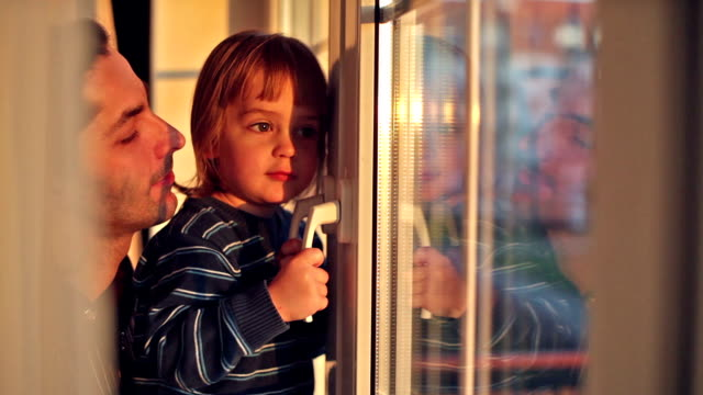 little boy with his father looks out the window