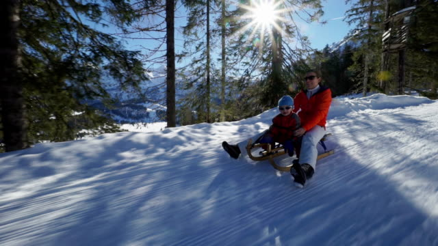 little boy with mom sledging on snow in forest - skijacke stock-videos und b-roll-filmmaterial