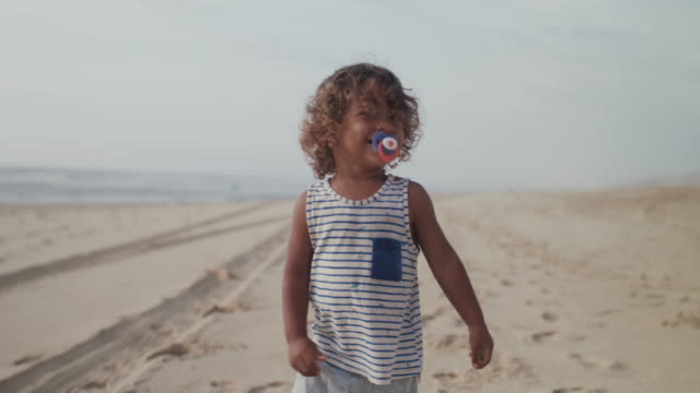 vidéos et rushes de little boy with pacifier running on the beach - s'enlacer