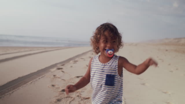 vidéos et rushes de little boy with pacifier running on the beach - tout petit