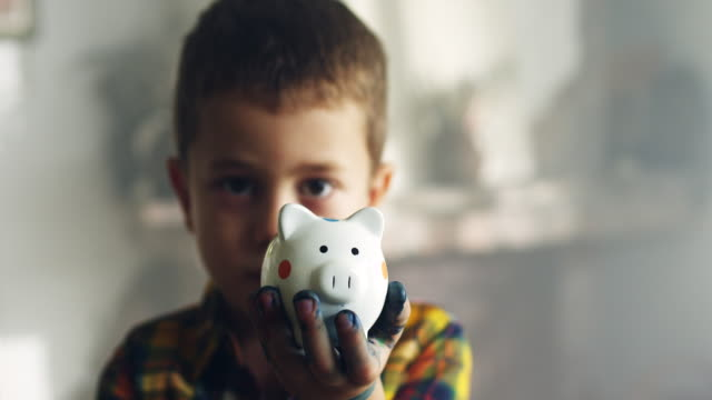 little boy with piggy bank - home finances stock videos & royalty-free footage