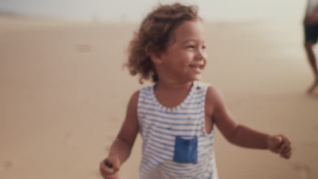vidéos et rushes de little boy with stick running with his father on the beach - rire