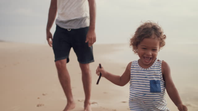 vidéos et rushes de little boy with stick running with his father on the beach - tout petit