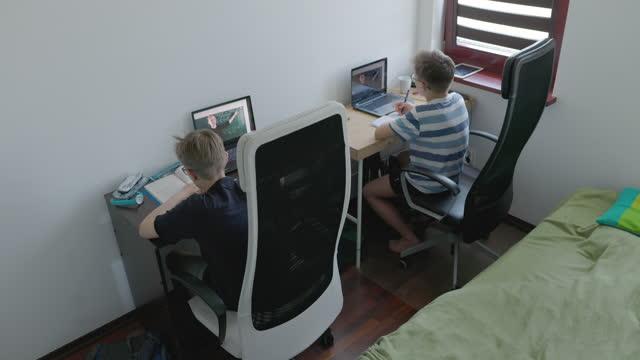 vidéos et rushes de petits garçons s'assistant à la classe en ligne de leur chambre - enseigner