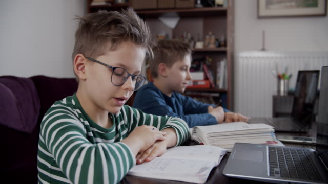 little boys attending to online school class. - educazione video stock e b–roll
