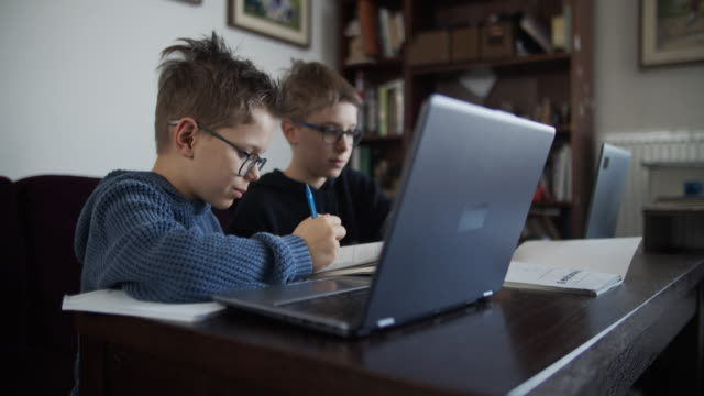 little boys attending to online school class. - moving activity stock videos & royalty-free footage