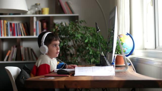vidéos et rushes de petits garçons s'occupant de la classe d'école en ligne. - e learning