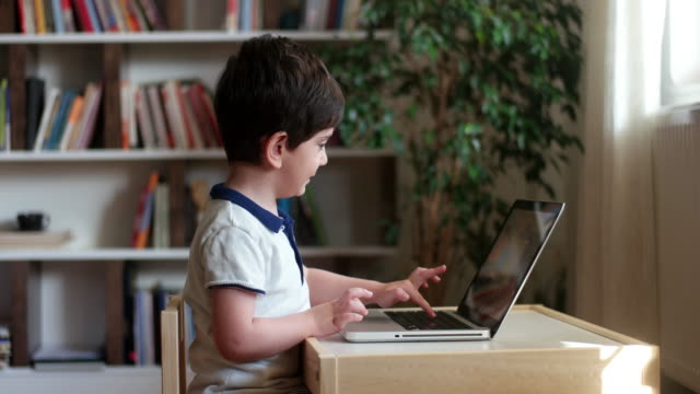 little boys attending to online school class. - quaderno video stock e b–roll