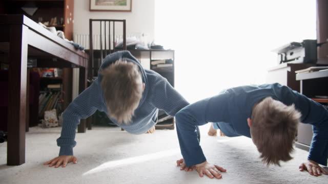 vídeos y material grabado en eventos de stock de niños pequeños haciendo flexiones en casa - flexiones
