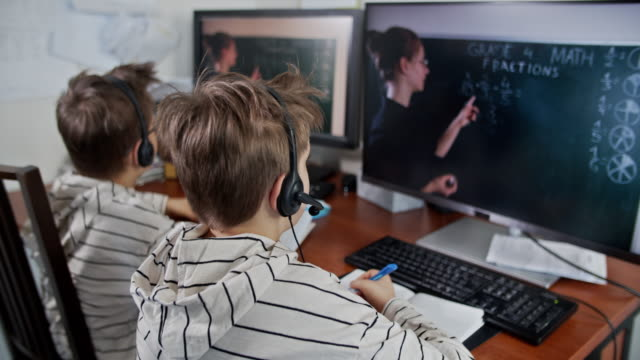 little boys during covid-19 quarantine attending to online school class. - educazione video stock e b–roll