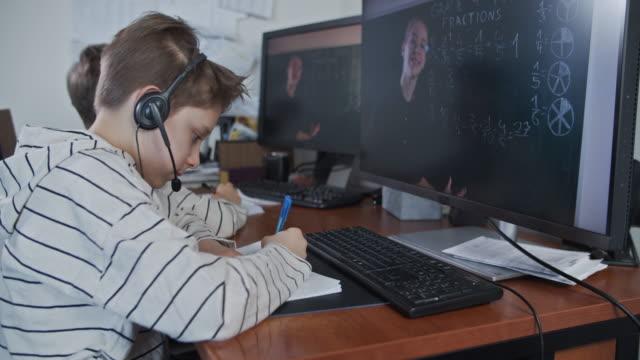 stockvideo's en b-roll-footage met kleine jongens tijdens covid-19 quarantaine bijwonen van online school klasse. - e learning