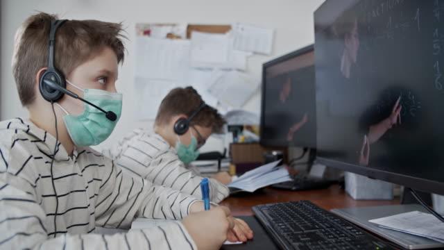 vídeos y material grabado en eventos de stock de niños pequeños durante la cuarentena covid-19 asistiendo a la clase de la escuela en línea. - orden de permanecer en casa