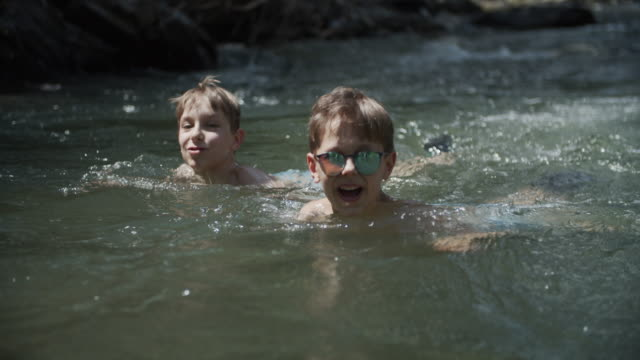little boys enjoying swimming in cold mountain river - recreational pursuit stock videos & royalty-free footage
