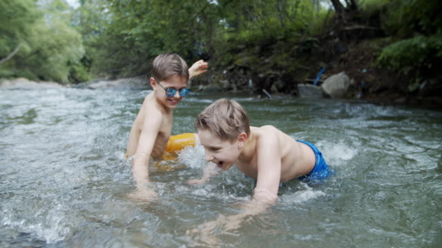 little boys enjoying swimming in the cold mountain river - walking in water stock videos & royalty-free footage