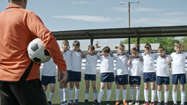 vidéos et rushes de little boys in soccer uniform listening to coach on stadium - s'entraîner