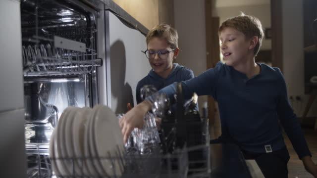 vidéos et rushes de petits garçons chargeant le lave-vaisselle après le repas - lave vaisselle
