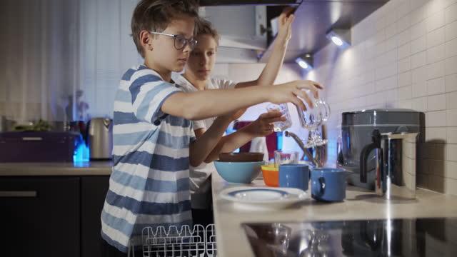 små pojkar laddar diskmaskinen - ansvar bildbanksvideor och videomaterial från bakom kulisserna