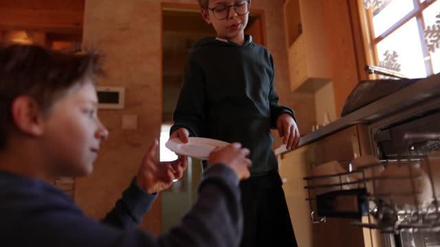 vidéos et rushes de petits garçons chargeant le lave-vaisselle - lave vaisselle