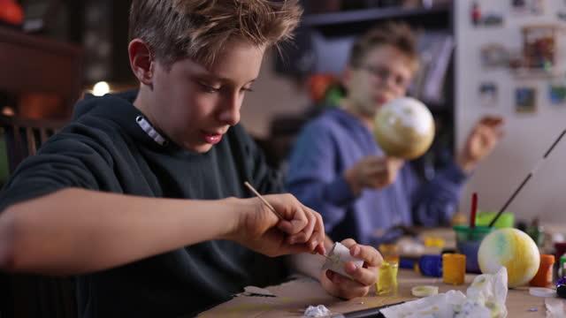 stockvideo's en b-roll-footage met kleine jongens die zonnesysteemmodel thuis maken - 10 11 jaar