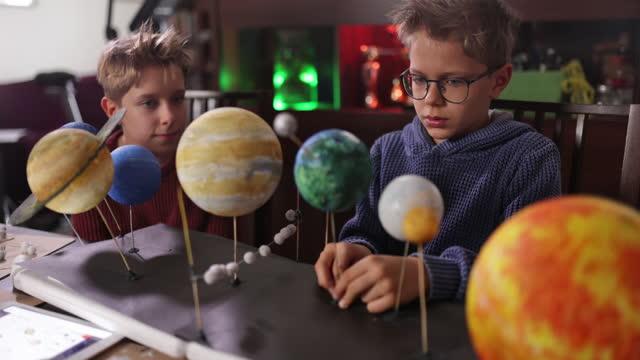 ragazzini che fanno il modello di sistema solare a casa - astronomia video stock e b–roll