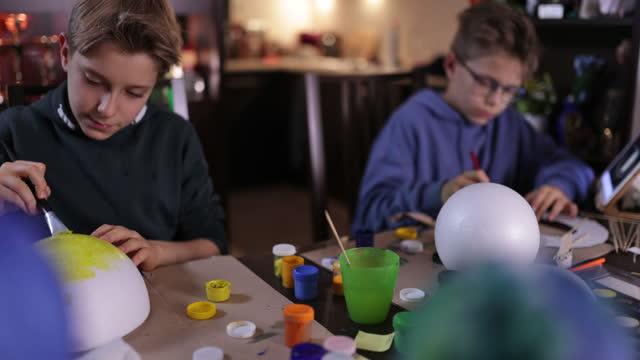vídeos de stock e filmes b-roll de little boys making solar system model at home - zoom out