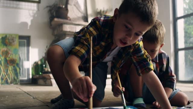 Little boys painting at the artist's studio