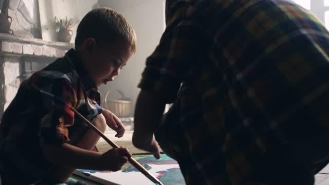 little boys painting at the artist's studio - tela di canapa video stock e b–roll