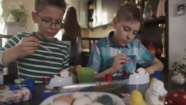 vídeos de stock e filmes b-roll de little boys painting easter eggs - páscoa