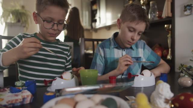 vídeos de stock e filmes b-roll de little boys painting easter eggs - domingo de páscoa
