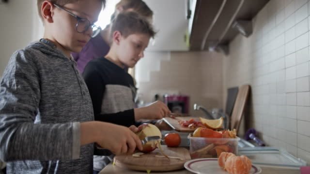 little boys peeling some fruit in kitchen and collecting organic waste - lavori domestici video stock e b–roll