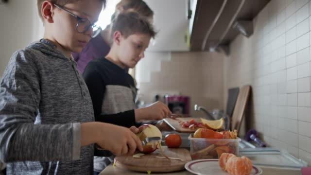 små pojkar peeling lite frukt i köket och samla organiskt avfall - hushållssyssla bildbanksvideor och videomaterial från bakom kulisserna
