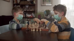 Little boys playing chess together during a virus outbreak