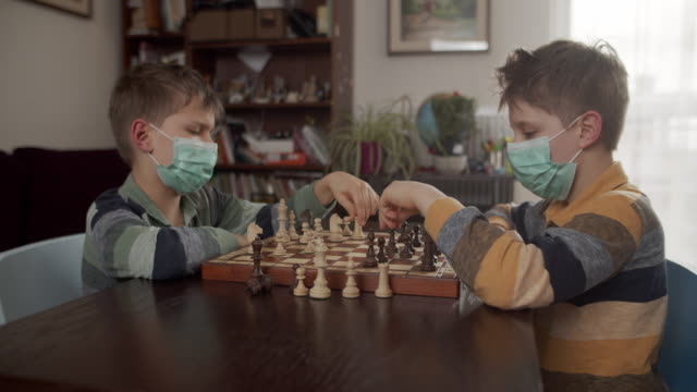 vídeos de stock e filmes b-roll de little boys playing chess together during a virus outbreak - 10 11 anos