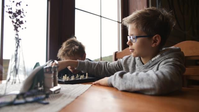 一緒にチェスをしている小さな男の子 - 余暇 ゲームナイト点の映像素材/bロール